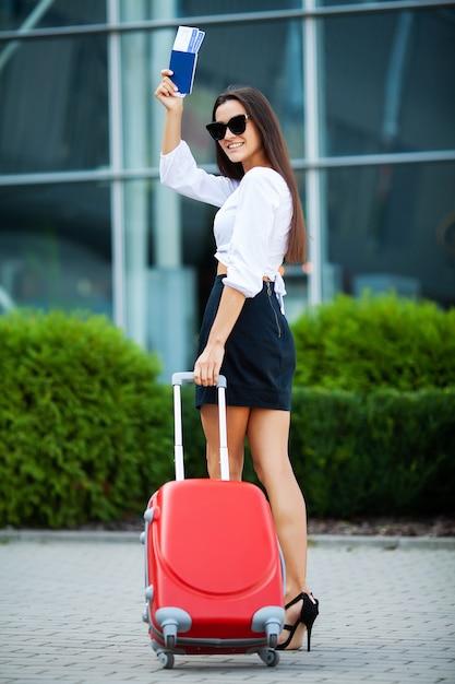 空港近くの赤いスーツケースを持つかなりビジネス女性 Premium写真