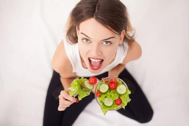 Жизнерадостная женщина ест овощной салат Premium Фотографии