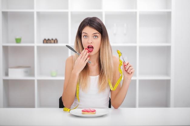 栄養障害のクレイジーダイエットの彼女の食べ物のシンボルとして若い女性や十代の少女持株皿 Premium写真