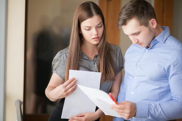 専門家の幸せな若いカップルは現代的なガラス事務所に立っています。 Premium写真