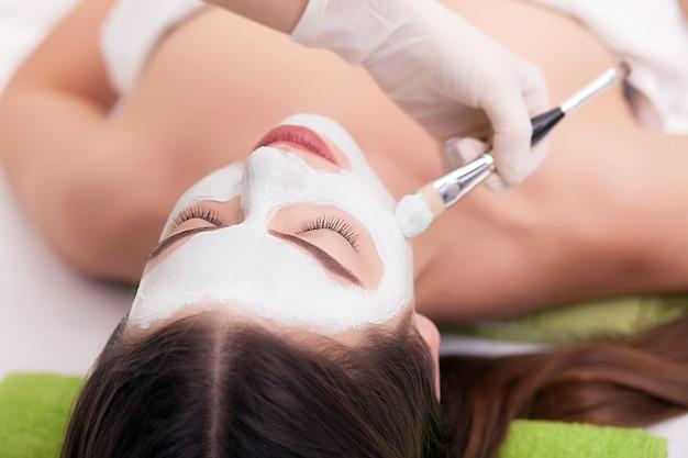 スパのコンセプト。スパサロンで女性の顔に栄養マスクを適用する手 Premium写真