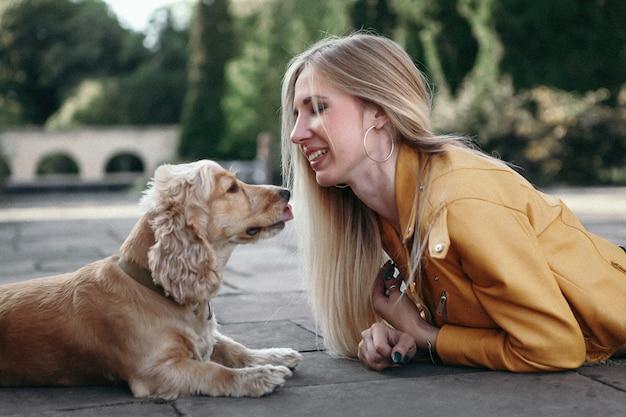 犬と少女は公園を散歩し、美しい夏の日を楽しんでいます。 Premium写真