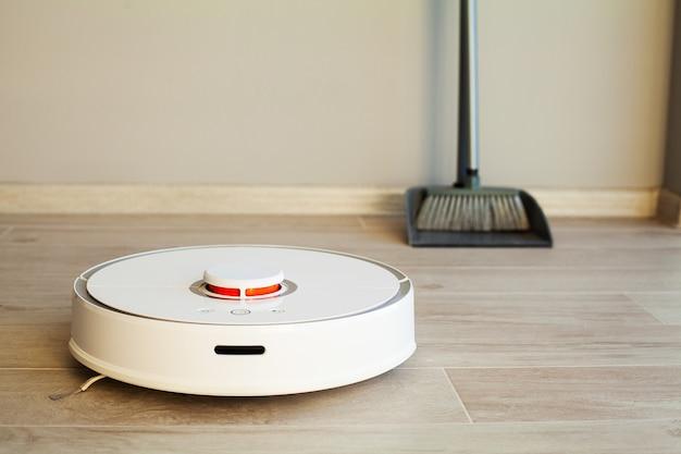 Умный дом, робот-пылесос выполняет автоматическую уборку квартиры в определенное время Premium Фотографии