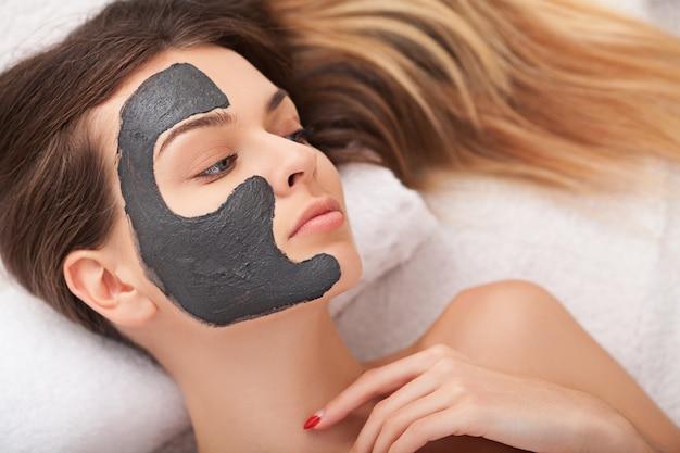 フェイシャルスキンケア。美しい女性のサロンで化粧品のマスクを取得 Premium写真