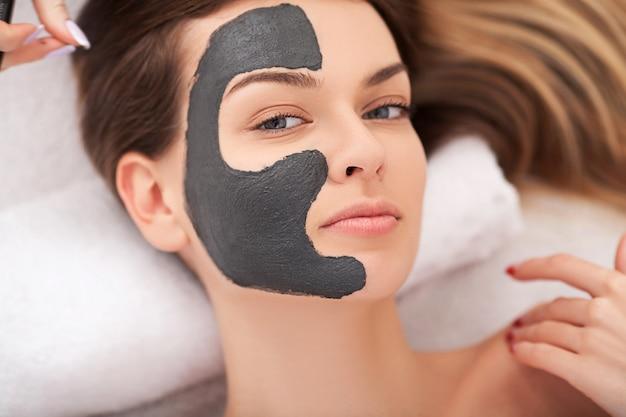 スパ。彼女の顔に粘土マスクを持つ魅力的な面白い女性 Premium写真