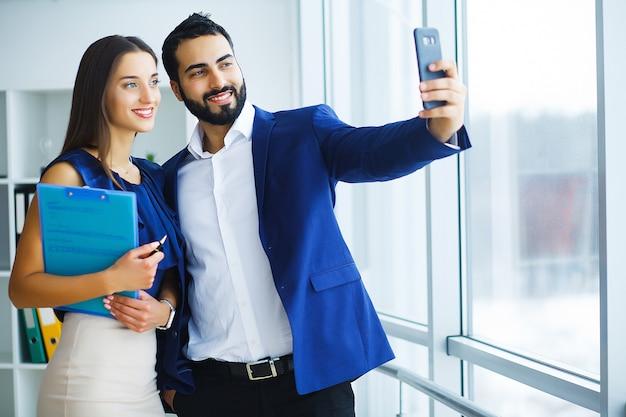 かなり混血の女性と彼女のあごひげを生やした同僚のラップトップを使用してオフィス会社での共同プロジェクトを議論するために Premium写真