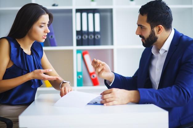 ビジネスマンが仕事上の問題に葛藤し、怒っている上司が同僚のビジネスマンや女性たちに悲鳴を上げると主張する Premium写真