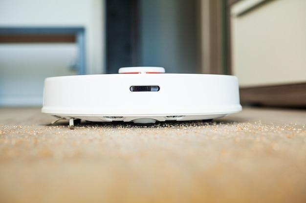 ロボット掃除機は、特定の時間にアパートの自動清掃を実行します。スマートホーム。 Premium写真