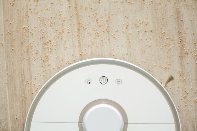Робот-пылесос выполняет автоматическую уборку квартиры в определенное время. умный дом. Premium Фотографии