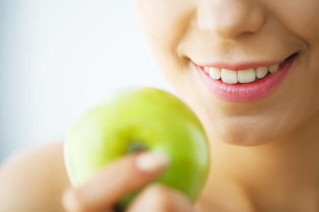 Красивая девушка с белыми зубами кусает яблоко. | Премиум Фото
