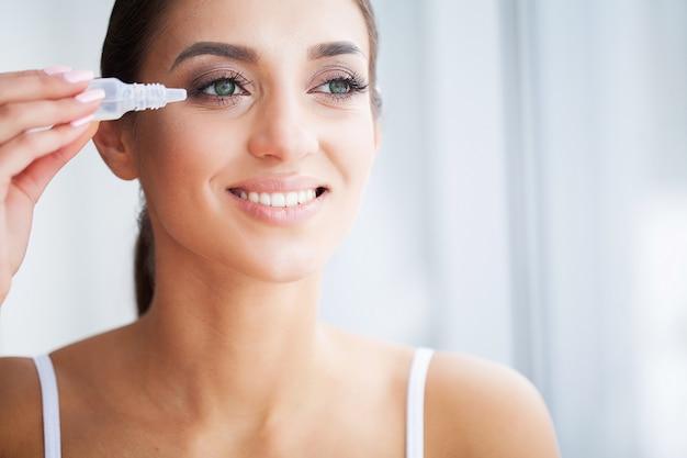 美容と健康。アイケア。美しい若い女性は目のために値下がりしました。グッドビジョン新鮮な表情で幸せな女の子 Premium写真