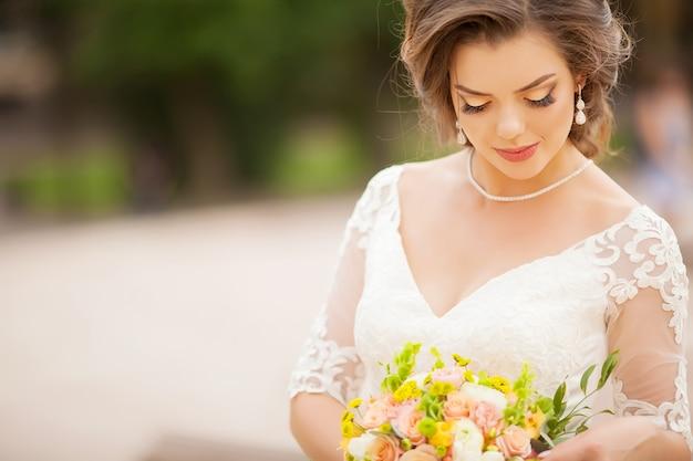 花を持つ若い美しい魅力的な花嫁の肖像画。 Premium写真