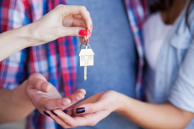 面白い若いカップルを楽しんで、新しい家への移動を祝います。 Premium写真