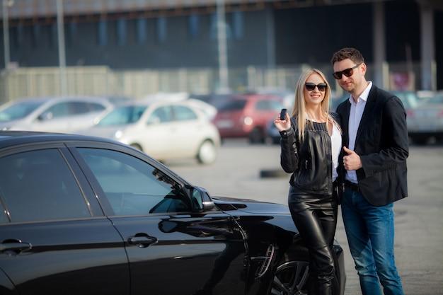 幸せなカップルが新しいモダンな黒い車を買う Premium写真