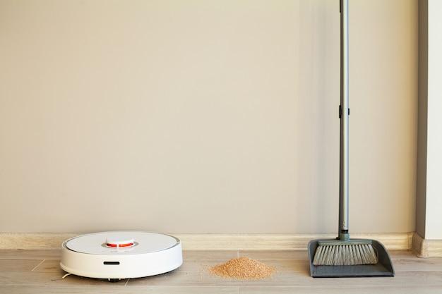 Сравнение робота-уборщика и метлы в светлой комнате Premium Фотографии