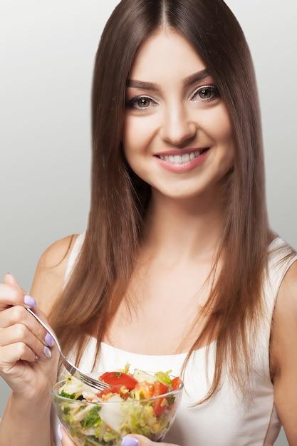 サラダを食べる若い女性の肖像画。 Premium写真