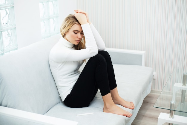 自宅で妊娠検査結果を見た後に落ち込んで悲しい気持ちの若い女性 Premium写真