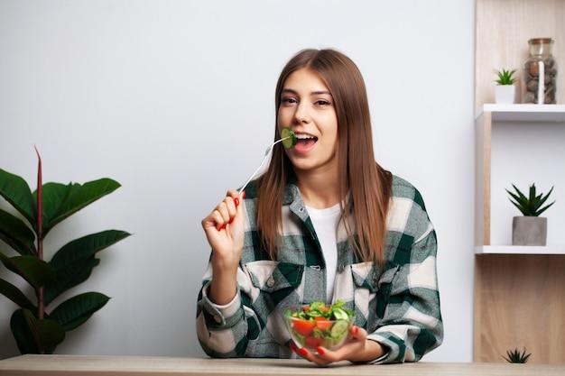 女の子は健康的な食品と有害な食品のどちらかを選択します Premium写真