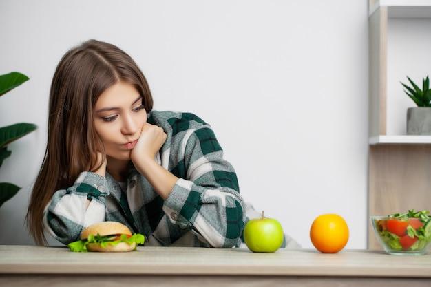 かわいい女性は健康的な食品と有害な食品のどちらかを選択します Premium写真