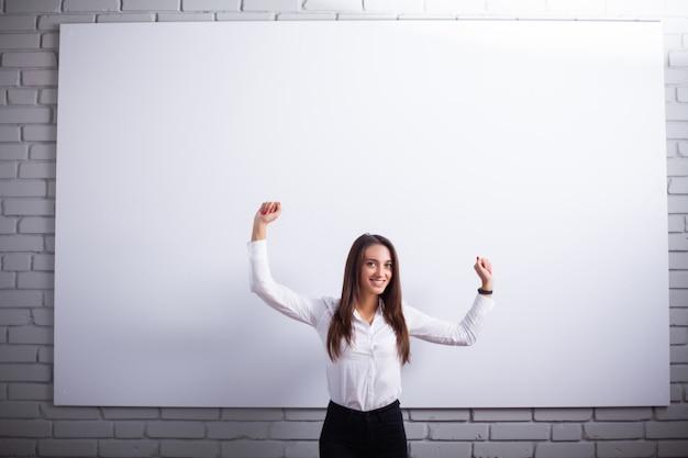 Портрет счастливой молодой женщины коммерсантки близко на белой стене. Premium Фотографии