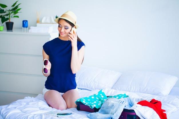 Красивая женщина собирает одежду в чемодан путешествия Premium Фотографии