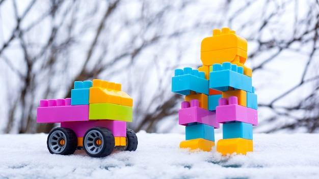 冬の新年の子供のおもちゃの車とロボット。路上で雪の中でおもちゃ。クリスマスプレゼント Premium写真