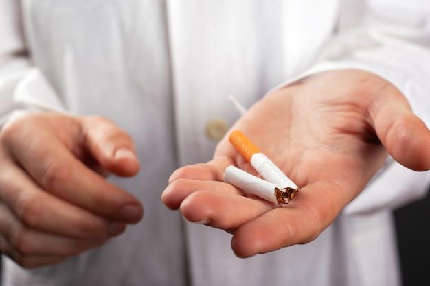 Доктор держит сломанную сигарету в руке. вред от курения. рак легкого вреден от никотина. Premium Фотографии