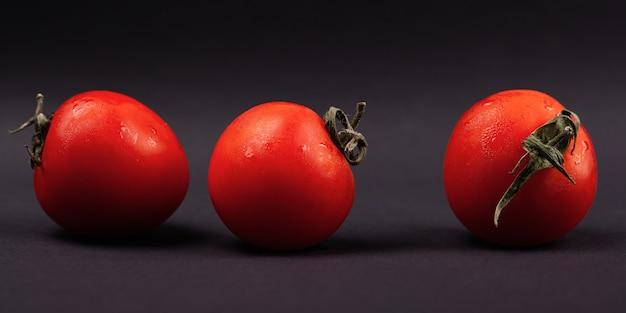 暗い背景のクローズアップ、パノラマに赤いトマト。 Premium写真
