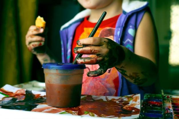 水彩で汚れた少女。カラフルな塗料でペイントすることを学ぶ子供 Premium写真