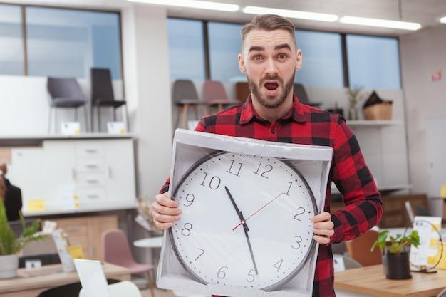 Красивый бородатый мужчина, глядя перегружены, держа большие настенные часы в мебельном магазине Premium Фотографии
