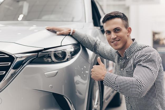 若い男がディーラーで新しい車を買う Premium写真