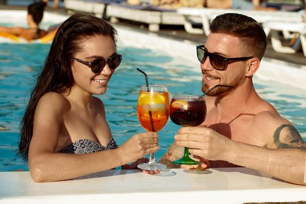 Счастливая любящая молодая пара с напитками в бассейне. концепция Premium Фотографии
