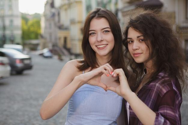 Счастливые женщины, улыбаясь в камеру, показывая сердце своими руками, копией пространства Premium Фотографии