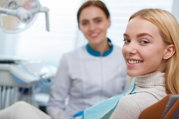 歯科用の椅子に座って、カメラに笑顔完璧な歯を持つ豪華な女性 Premium写真