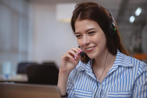 コールセンターで働くヘッドセットを持つフレンドリーなカスタマーサポートオペレーター Premium写真