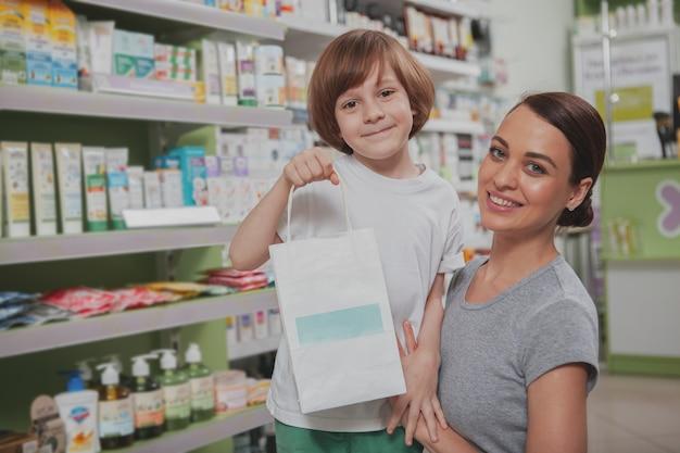 Красивая женщина, покупки в аптеке со своим маленьким сыном Premium Фотографии