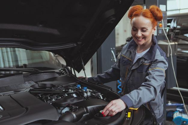 Женский механик работает на автосервисе Premium Фотографии