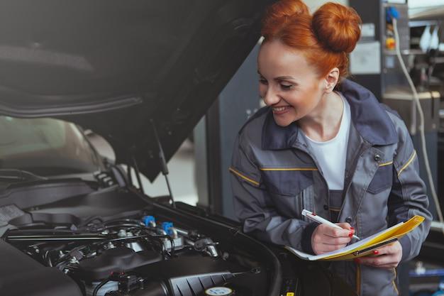 車のサービスステーションで働く女性のメカニック Premium写真