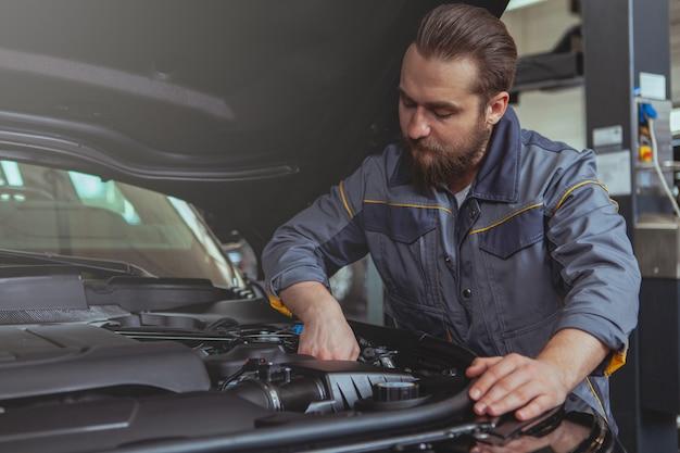 車のサービスステーションで働くひげを生やしたメカニック Premium写真