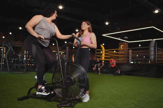 Красивые спортсменки больших размеров вместе занимаются в тренажерном зале Premium Фотографии