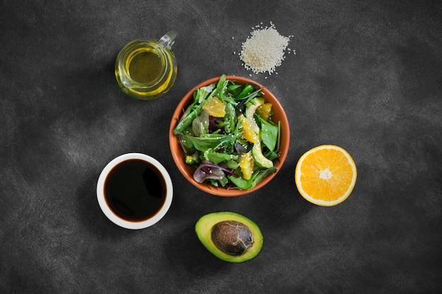 黒いテーブルの上の食材と新鮮なサラダ Premium写真