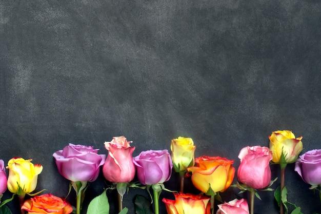 Фиолетовые и желтые розы, коробка присутствует на черном фоне Premium Фотографии