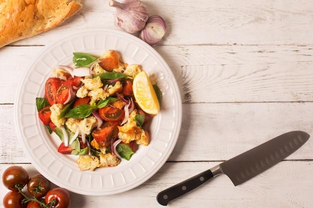 イタリアの前菜サラダ、トマト、パン、バジル Premium写真