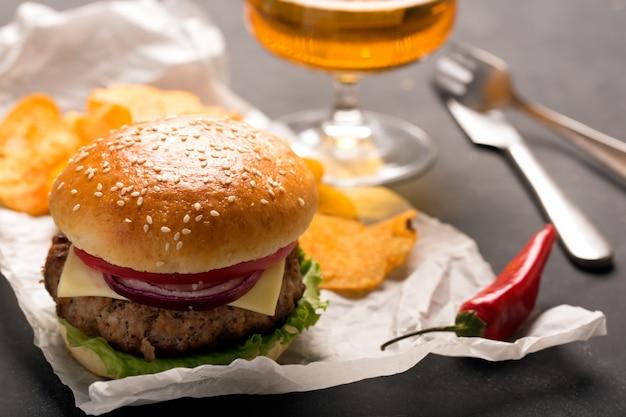 Гамбургер с мясной котлетой. картофельные чипсы и пиво Premium Фотографии