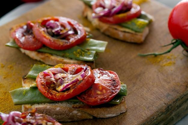 揚げ赤玉ねぎ、トマト、インゲン豆を使った夏のサンドイッチ Premium写真