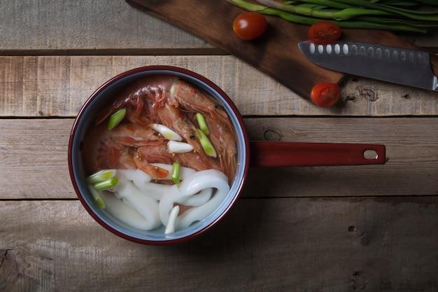 Традиционный тайский суп том ям на деревянном столе Premium Фотографии