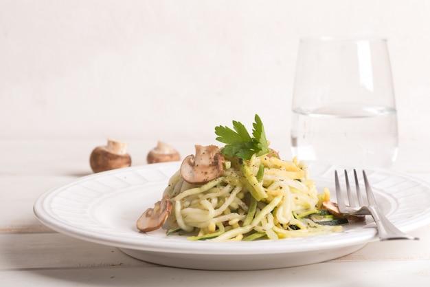 Тарелка спагетти, приготовленная из цуккини и грибным соусом на деревянном столе Premium Фотографии