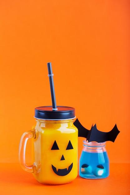 オレンジ色の背景に怖い顔でガラスの瓶にハロウィーンの健康的なカボチャやニンジンを飲む Premium写真