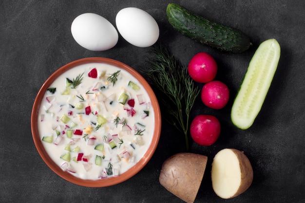 オクローシカ。テーブルの上の野菜と伝統的なロシアの夏のヨーグルトの冷たいスープ Premium写真