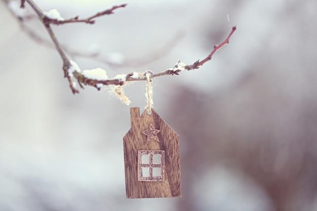 クリスマスの時期。小さな木造の家が枝に揺れ、大きな雪の結晶がゆっくりと落ちます。 Premium写真